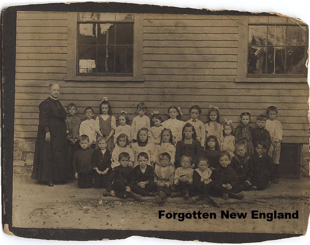 A group of Lowell schoolchildren, with their teacher, in front of their schoolhouse